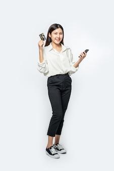 Ze was gekleed in een wit overhemd en een donkere broek om te gaan winkelen en hield een creditcard en smartphone vast