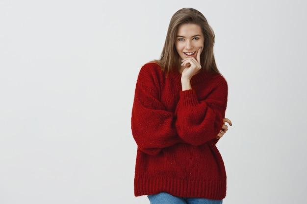 Ze weet precies hoe te verleiden met blik. sassy knappe flirterige europese vrouw in losse rode de wintersweater bijtende vinger grijnzend met interessant idee in gedachten