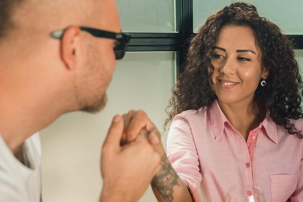 Ze zei hem ja. close-up van de jonge man die zijn vrouw hand kust terwijl hij buiten een huwelijksaanzoek doet.