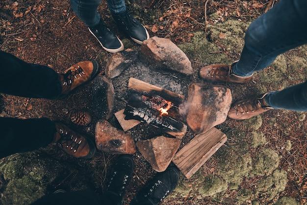 Ze zullen zich deze dag herinneren. close-up bovenaanzicht van jonge mensen die rond het kampvuur staan tijdens het wandelen in het bos