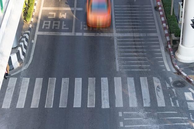 Zebrapad en auto, bezige stadsstraat en auto in motieonduidelijk beeld op zebrapad