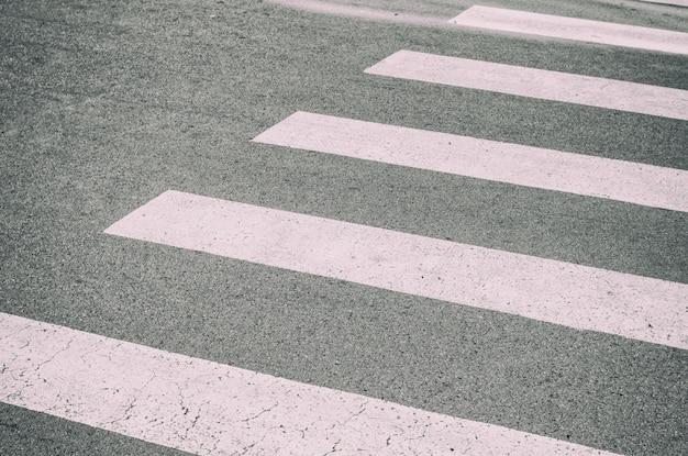 Zebrapad geschilderd op het asfalt, detail van een signaalcirculatie, verkeersinformatie voor voetgangers en automobilisten, veiligheid in betonnen jungle-concept