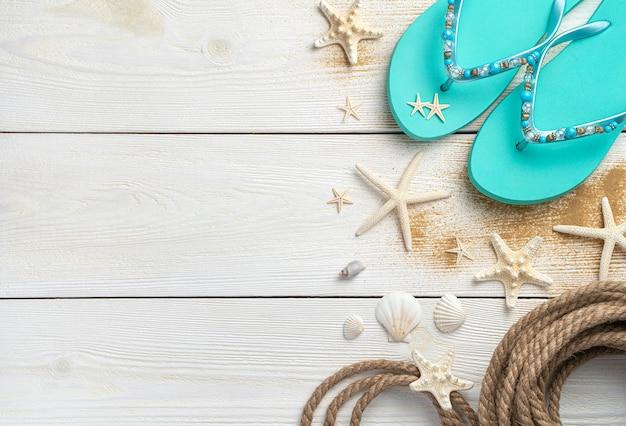 Zee achtergrond met schelpen, touw en zomer slippers op een witte houten achtergrond.
