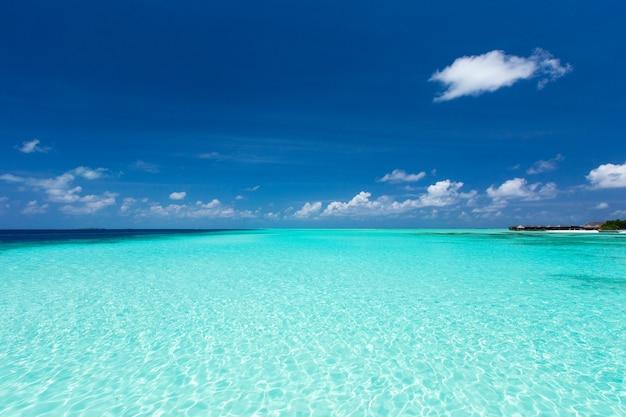 Zee en blauwe lucht. blauw zeewater en lucht met witte pluizige wolken. horizontale achtergrond van blauwe zee. tropisch landschap