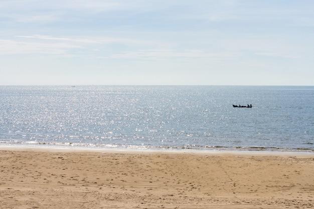 Zee en strand met vissersboot op zomerochtend