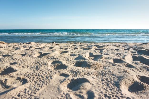 Zee met blauwe lucht en strand zand aard.