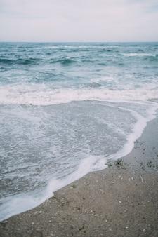 Zee met de golven die op het strand beuken en zeespray creëren.