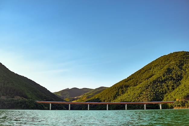 Zee met een betonnen brug erop, omgeven door heuvels bedekt met bossen onder het zonlicht