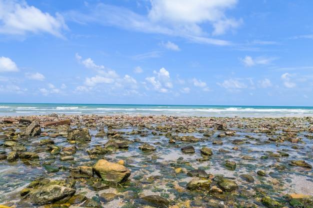 Zee met steen en blauwe lucht