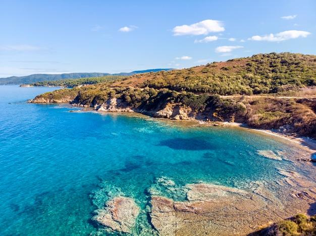 Zee met strand en bergen in nea roda, halkidiki, griekenland