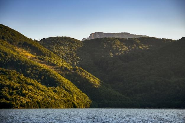 Zee omgeven door heuvels bedekt met bossen onder het zonlicht en een blauwe lucht