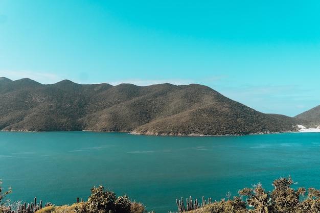 Zee omgeven door heuvels bedekt met groen onder een blauwe lucht en zonlicht in rio de janeiro