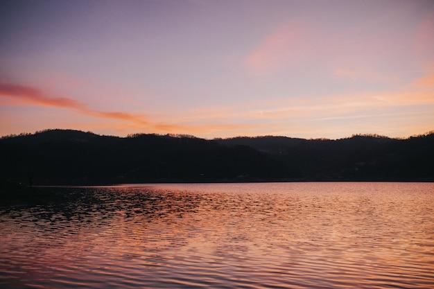 Zee omgeven door heuvels onder het zonlicht tijdens een prachtige zonsondergang