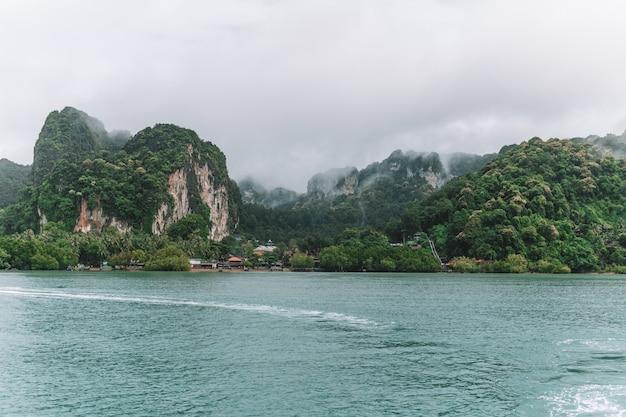 Zee omgeven door rotsachtige heuvels bedekt met groen en mist overdag