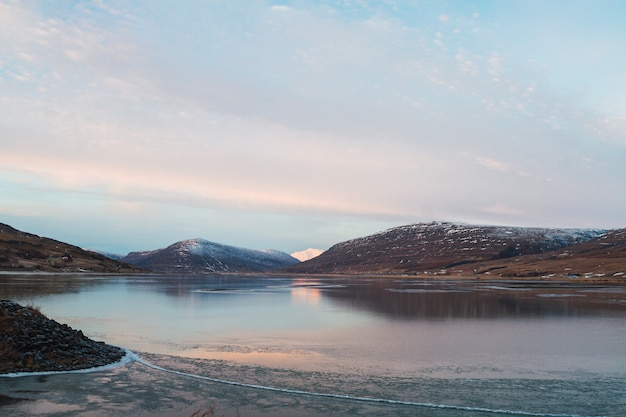 Zee omgeven door rotsen bedekt met de sneeuw en nadenken over het water in ijsland
