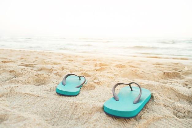 Zee op het strand voetafdruk mensen op het zand en slipper van voeten in sandalen schoenen op strandzand