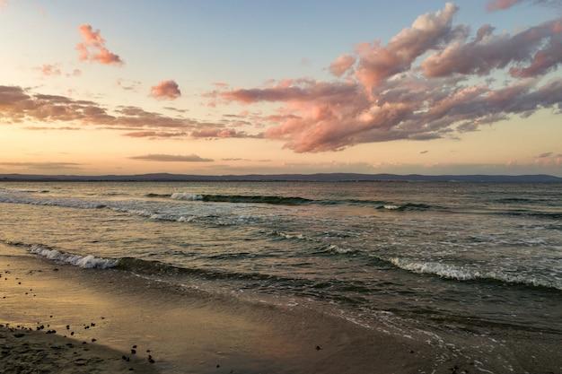 Zee oppervlak met blauwe water golven onder gele en paarse avondrood.