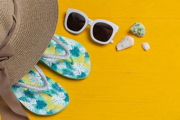 Zee reizen, hoed, zonnebril, bril, sandalen gelegd op een gele houten vloer.