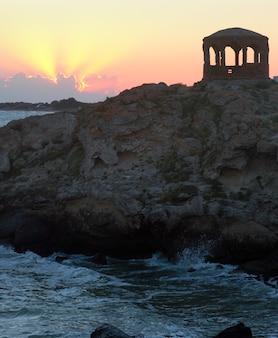 Zee surf golfonderbreking op kustlijn en kaap met paviljoen. twee schoten samengesteld beeld.