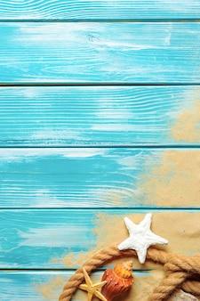 Zee touw met veel verschillende zeeschelpen op het zeezand op een blauwe houten achtergrond. bovenaanzicht