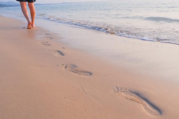 Zee vakantie. iemand die op het strand loopt. strandreis, mens die op zandstrand lopen die voetafdrukken in het zand verlaten. close-updetail van mannelijke voeten en gouden zand. selectieve aandacht. spoor op blote voeten