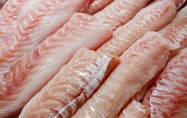 Zeebaars, ham, grouper vis, zeebaars filet veel stukken gesneden opgestapelde bulk in vismarkt.