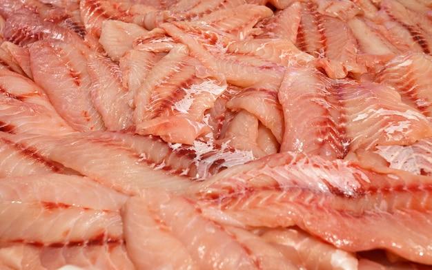 Zeebaars rauw, ham, grouper vis, zeebaars filet gesneden en in bulk in vismarkt opgestapeld.