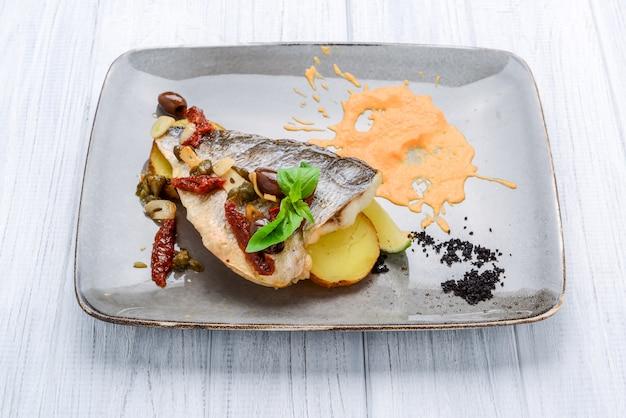 Zeebrasemvissen met aardappel op witte plaat