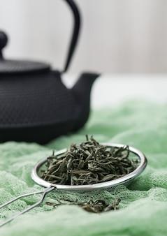 Zeef-infuser met losse groene biologische thee op groene doek met zwarte japenese ijzeren theepot.
