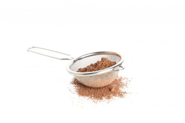 Zeef met cacaopoeder dat op wit wordt geïsoleerd