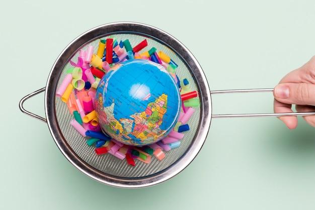 Zeef met plastic en wereldbol