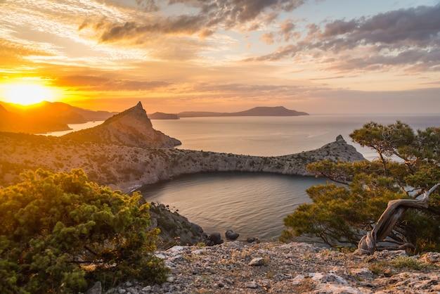 Zeegezicht bij zonsopgang in de bergen