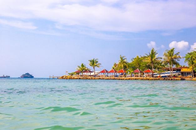 Zeegezicht, heldere paviljoens aan de oevers van de azuurblauwe zee op het eiland