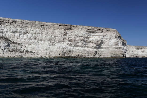 Zeegezicht, hoge rotsachtige kust en donkerblauw wateroppervlak van zee.