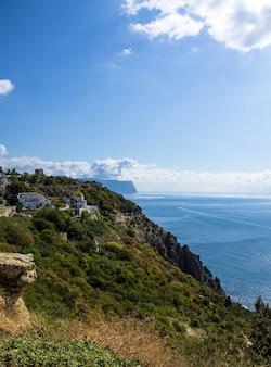Zeegezicht, lucht, bergen, zee, grote stenen aan de kust.