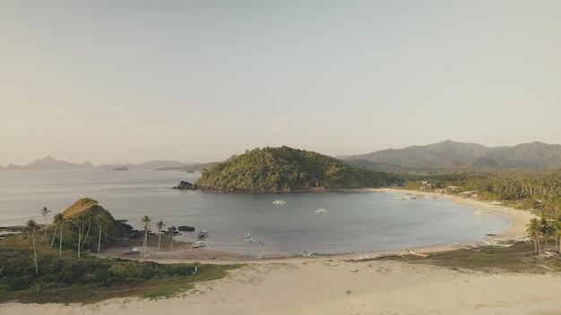 Zeegezicht met boten bij groene bergantenne. zandstrand, palmbomen op heuvels aan zee baai. niemand