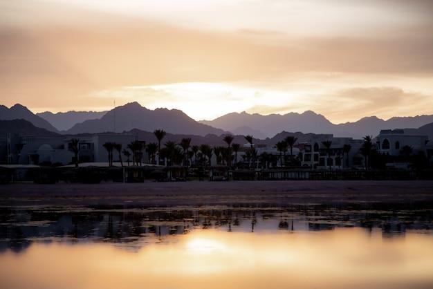 Zeegezicht met een reflecterende hemel. de zon gaat onder boven de stad bij de bergen.