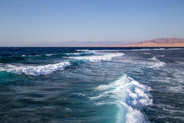 Zeegezicht met geweven golven en bergsilhouetten aan de horizon.