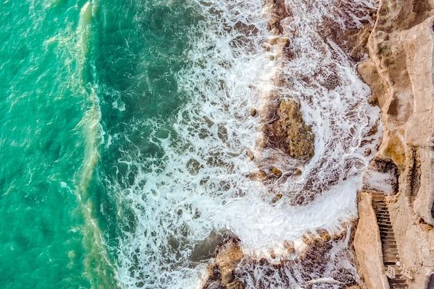 Zeegezicht met golven die tegen de rotsen breken