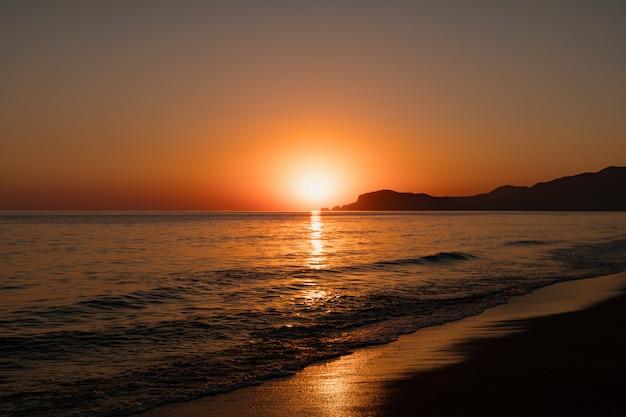 Zeegezicht met heldere hemel en golven op zonsondergang