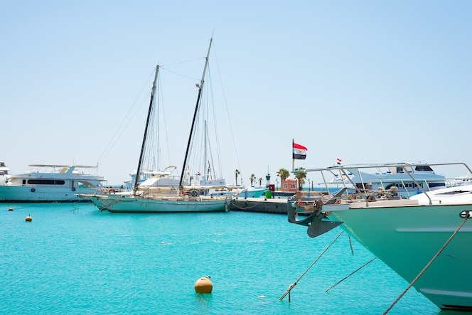 Zeegezicht met parkeerplaats en verankerde boten en schepen.