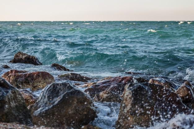Zeegezicht met rotsen, schuim en spray van de golven