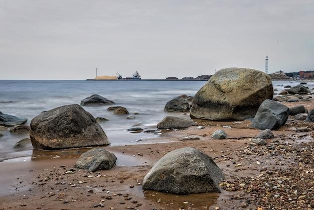 Zeegezicht met stenen en boten op de pier