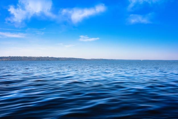 Zeegezicht met zee horizon en bijna heldere diepblauwe hemel - achtergrond.