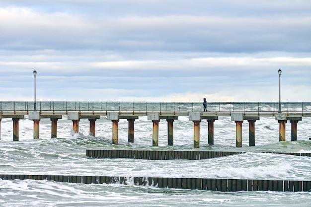 Zeegezicht, pier en vintage lange houten golfbrekers die zich uitstrekken tot ver in zee. persoon die over de brug over zee loopt. winterlandschap van de oostzee.