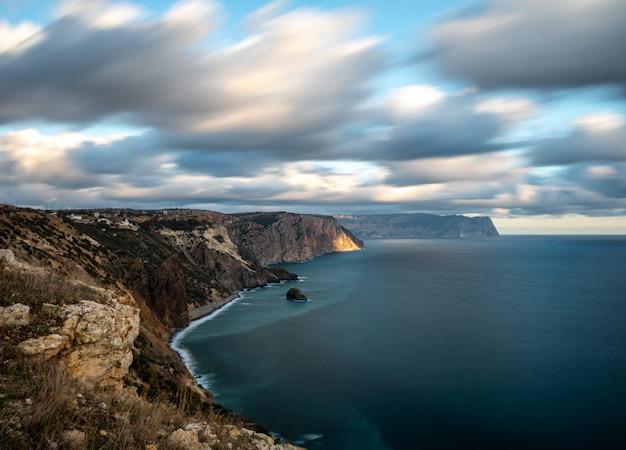Zeegezicht van de kalme zee met wolken en heldere hemel