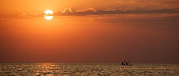 Zeegezicht van nog steeds zeeoppervlak, man op boot en gouden zonsondergang in de lucht op heldere zomerdag