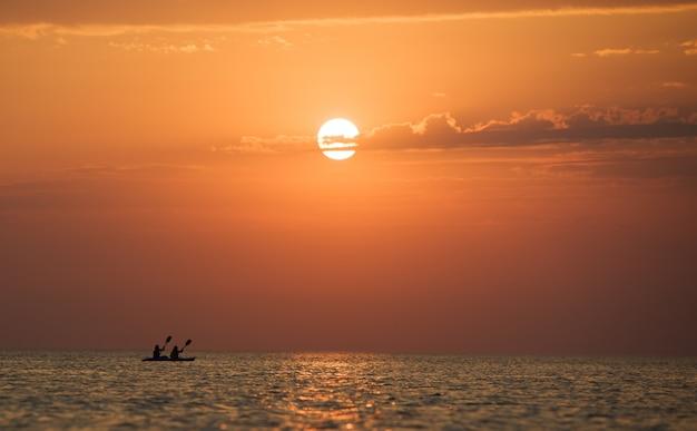 Zeegezicht van nog steeds zeeoppervlak, mannen op boot en gouden zonsondergang in de hemel