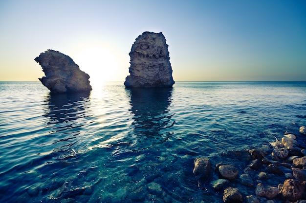Zeegezicht van nog steeds zeewaterkust, steenachtige bodem en rotsen in overzees