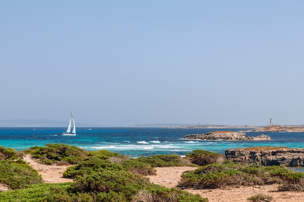 Zeegezicht voor de kust van ibiza met prachtige blauwe zee en een zeiljacht